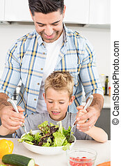 Smiling father tossing salad with his son at home in kitchen