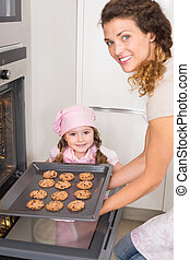 Mother taking cookies out of the oven with daughter at home...