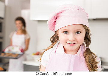 Little girl wearing pink apron and chefs hat smiling at camera