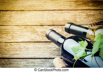 Bottles of red and white wine on wooden background
