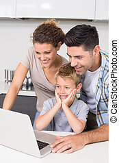 Parents using laptop with their son at home in kitchen