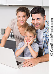 Smiling parents using laptop with their son at home in...