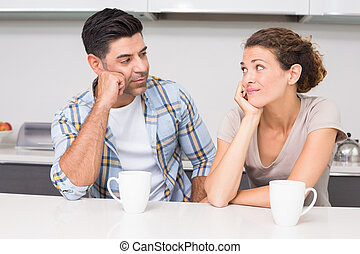 Fed up couple having coffee looking at each other at home in...