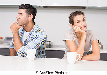 Troubled couple having coffee not talking at home in kitchen