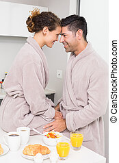 Romantic couple in bathrobes having breakfast together at...