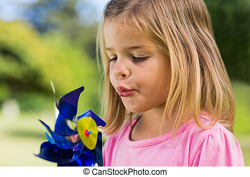 Cute girl blowing pinwheel at park - Close-up of cute girl...