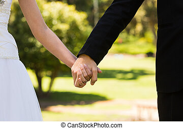 Mid section of newlywed couple holding hands in park -...