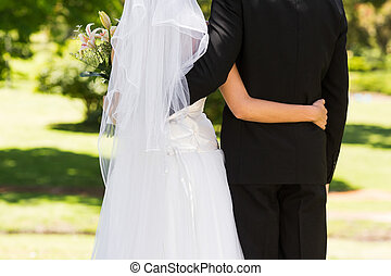Mid section of a newlywed with arms around in park - Rear...