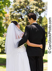Rear view of newlywed with arms around in park - Rear view...