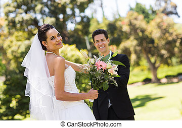 Happy newlywed couple with bouquet - Portrait of a happy...