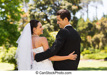 Newlywed couple with arms around in - Rear view of a...