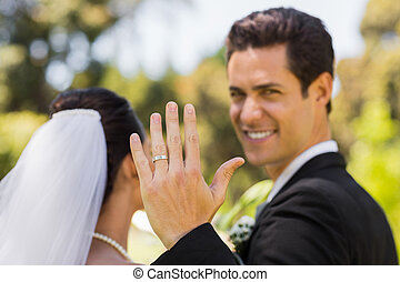 Bridegroom showing wedding ring to the camera in park -...