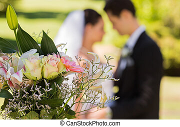 Bouquet with blurred newlywed couple in background at park -...