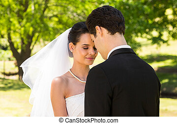 Romantic newlywed couple standing in park