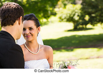 Romantic newlywed couple looking at each other in park -...