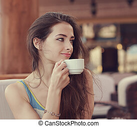 Beautiful smiling woman drinking coffee from cup and looking