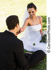 Groom kissing his beautiful bride's hand at park - View of a...