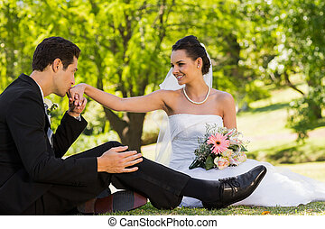 Groom kissing his bride's hand at park - View of a groom...