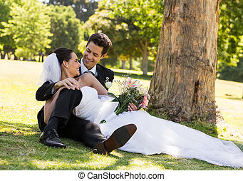Happy newlywed couple relaxing in park - Happy young...