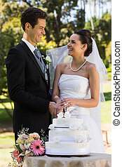 Newlywed couple cutting wedding cake at park - Happy young...