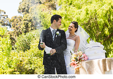Newlywed couple with groom opening champagne bottle at park...