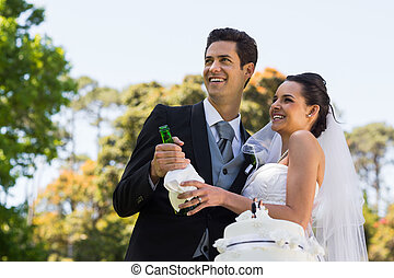 Newlywed couple with champagne bottle at park - Happy young...