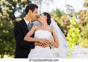 Newlywed about to kiss besides wedding cake at park - Happy...