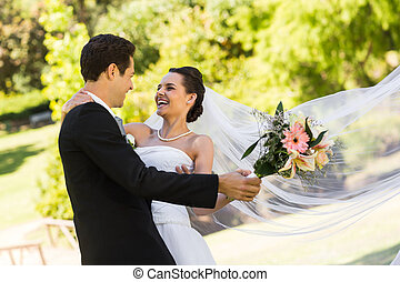 Cheerful newlywed couple dancing in park - View of a...