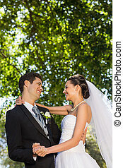 Romantic newlywed couple dancing in park - Side view of a...