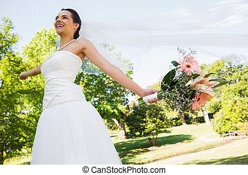 Cheerful young beautiful bride with bouquet in park - Low...