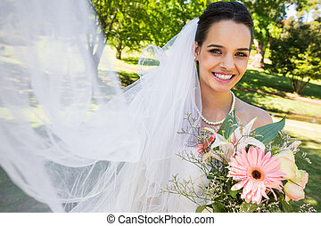 Smiling young beautiful bride with bouquet in park -...