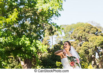 Cheerful bride throwing bouquet in park - Cheerful young...