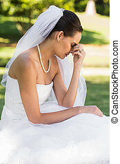 Beautiful worried bride sitting at park - Side view of a...