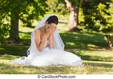Beautiful worried bride sitting at - View of a beautiful...