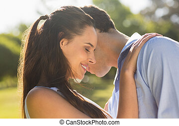 Loving and happy couple at park - Close-up side view of a...