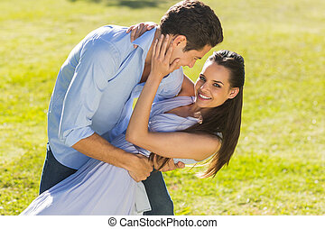 Loving and happy couple dancing in park - Side view of a...