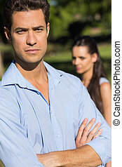 Man with blurred woman in background outdoors - Close-up of...