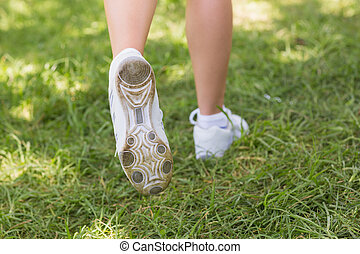 Low section of woman in sports shoes jogging at park -...