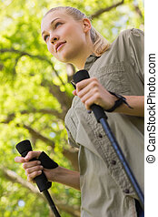 Beautiful young woman Nordic walking in park - Low angle...