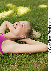 Relaxed beautiful woman lying on grass in park