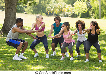 Group of fitness class exercising in park - Instructor with...