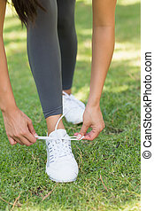 Low section of woman tying shoe lace at park - Close-up low...
