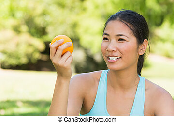 Close-up of woman holding orange in park