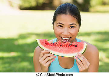 Portrait of a woman eating watermelon in park - Close-up...