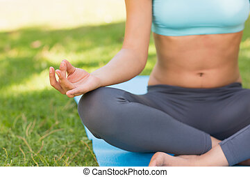 Close-up of a sporty woman in lotus pose at park - Close-up...
