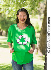 Smiling woman wearing green recycling t-shirt in park