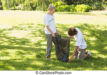 Volunteers picking up litter in park - Two young volunteers...