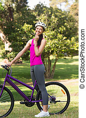 Fit woman with helmet and bicycle a - Portrait of a fit...