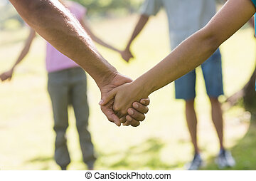Mid section of friends holding hands in park - Close-up mid...