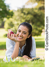 Smiling young woman reading a book in park - Portrait of a...